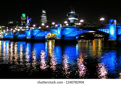 illuminated southwark bridge at night with modern light and water reflections with City skyline in background in London UK
