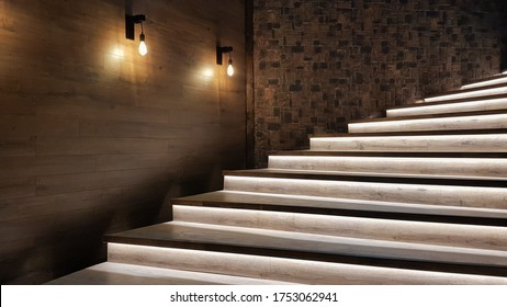 Illuminated staircase with wooden steps and illuminated at night in the interior of a large house