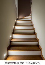 Illuminated staircase with wooden steps and white risers - modern interior