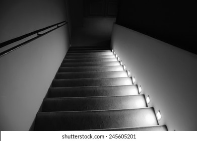 Illuminated stairs in the building. Suspense background. Black and white.