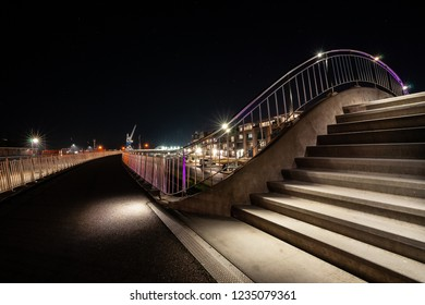 Illuminated steps with LED and different colors yellow, purple and blue as a viaduct spanning for train tracks near the boulevard along the harbor of Harlingen.