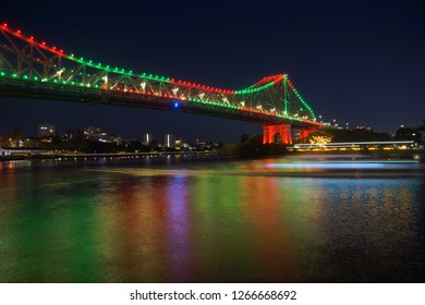 Illuminated Storybridge in red and green lights by night, with ferry motion blurs