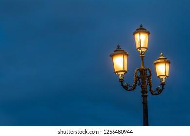 Illuminated street lights in Venice against a blue evening sky.