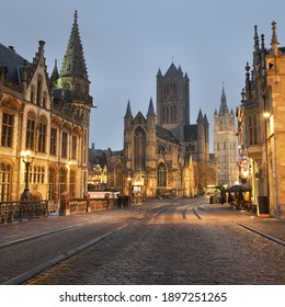 Illuminated street near St Michael bridge and St Bavo's Cathedral in a historical center of Ghent city. Night cityscape. Travel guide, national landmark, sightseeing theme. Belgium
