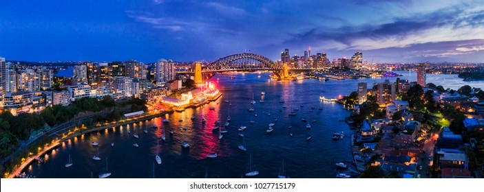 Illuminated sunset lights of major Sydney city landmars on Sydney harbour shores across both sides of Sydney Harbour bridge as seen over still waters of Lavender Bay in North Sydney.