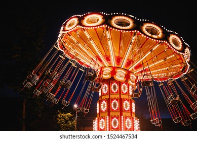 Illuminated swing chain carousel in amusement park at night - Shutterstock ID 1524467534