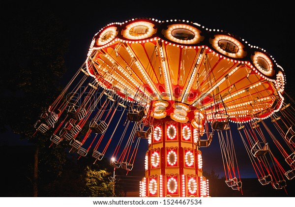 Illuminated swing chain carousel in amusement park at night
