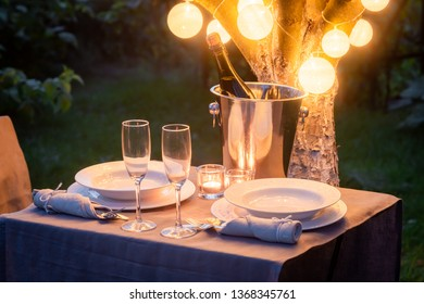 Illuminated table for two in green garden