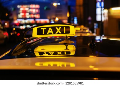 illuminated taxi sign on the roof of a taxi at night