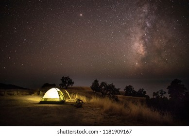 Illuminated tent under dark sky with stars and milky way shining bright above incredible camping site