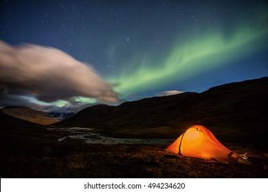 Illuminated Tent under Northern lights in the wilderness of Sweden - Kungsleden