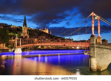 Illuminated tour boat sailing under a footbridge over the Saone river in Lyon at dusk.
