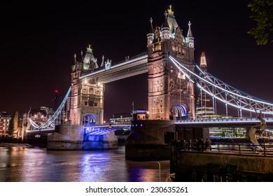 illuminated Tower Bridge at night, seen from northbank - London, UK