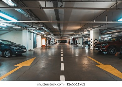 Illuminated underground car parking interior under modern mall with lots of vehicles and arrows on floor, toned