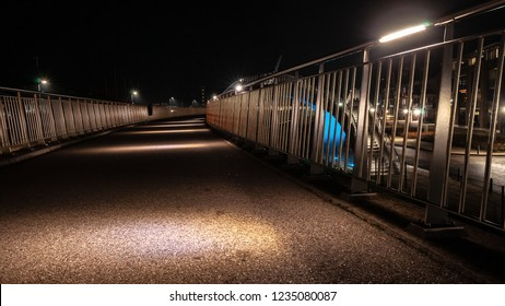 Illuminated walkway with metal silver balustrade in a curve shape.