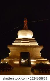 Illuminated white stupa next to the Potala Palace in Lhasa. Tibet, China