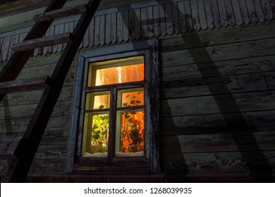 Illuminated window of a Russian Dacha at night.
