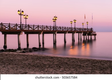 Illuminated wooden jetty on a beach in Marbella during sunset. Long exposure.