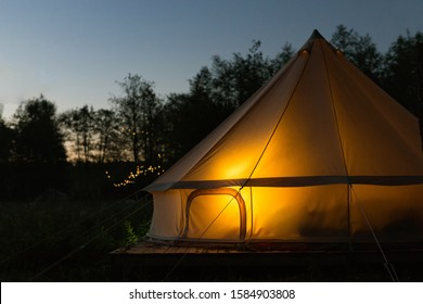 Illuminated yellow camping bell tent at night. Glamping bell tent glows at forest