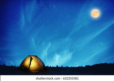 Illuminated yellow camping tent under many stars and full moon at night