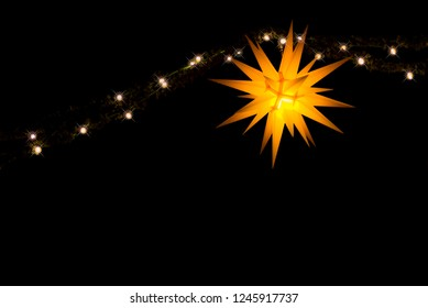 Illuminated yellow German Moravian Star and fairy lights with a black background