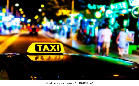Illuminated with yellow taxi taxi sign on a car roof at night.
