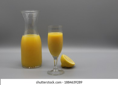 illuminating yellow juice in elegant champagne glass. carafe with juice and a half of lemon nearby. ultimate gray background. natural drink with vitamin c. still life, copy space