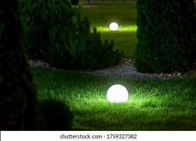 illumination backyard light garden with electric ground lantern with sphere diffuser lamp in the green grass lawn in outdoor park with landscaping, dark patio illuminate night scene nobody.
