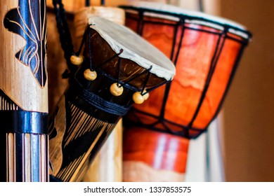 Illuminations in the form the reels and in the shape of an hourglass hanging on the wall. Ethnic African, Cuban, Latin percussion instruments