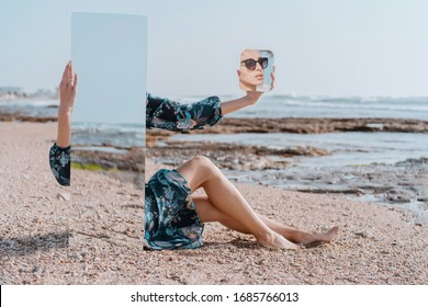 illusion portrait Stylish girl in sun glasses and dress sit on sea beach holding mirrors with reflection of sand and stones. New vision of fashion projects concept. Digital narcissism