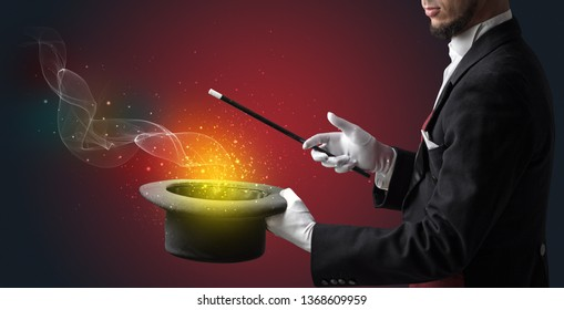 Illusionist hand starts to conjure with white glove and magic wand