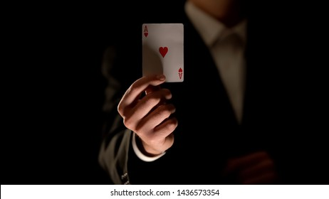 Illusionist showing ace of heart card at camera, magic trick, black background