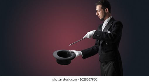 Illusionist white hand wants to conjure with magic wand from a black cylinder something - Shutterstock ID 1028567980
