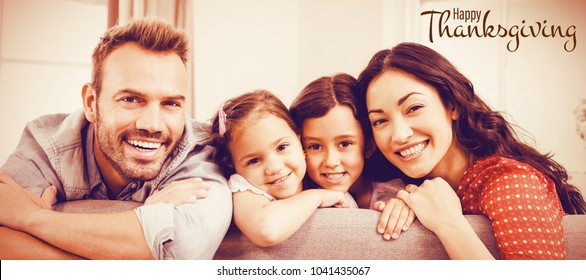 Illustration of happy thanksgiving day text greeting against portrait of happy family leaning on sofa