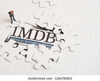 Illustrative editorial of 1MDB scandal concept - 1Malaysia Development Berhad criminal case-miniature figurine of a businessman looking at a jigsaw puzzle of 1MDB-with copy space
