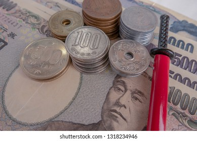 illustrative editorial of Japanese Yen in notes and coins and a miniature katana in red scabbard.