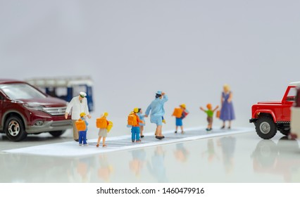 Illustrative editorial - Miniature toys school kids walk on cross road bar code - school children road safety concept.