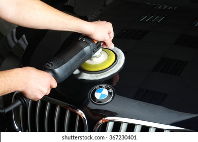 """Illustrative editorial. The worker polishes a car cowl with the electric tool. Car service """"Aquacars"""". Moscow. 04.10.2015."""