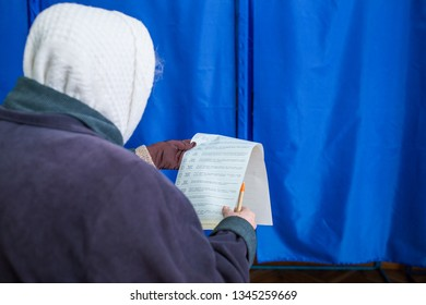 Illustrative image of the election in a democratic society. Elections in Ukraine Voting at a polling station. The elderly woman's voter gets acquainted with the contents of the ballot papers.