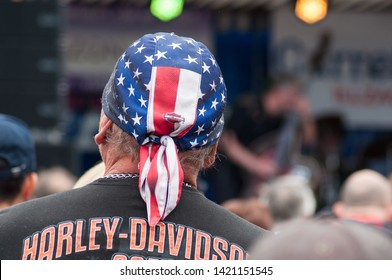 Illzach - France -9 June 2019 - Portrait of Harley Dadson biker with american flag on haed on back view at rock n roll concert at fun car show event