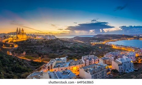 Il-Mellieha, Malta - Beautiful panoramic skyline view of Mellieha town at blue hour with Paris Church and Mellieha beach and Gozo at background with blue sky and clouds