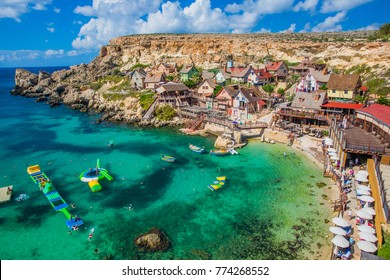 Il-Mellieha, Malta - Panoramic skyline view of the famous Popeye Village at Anchor Bay with traditional Luzzu boats, beautiful colorful clouds and sky
