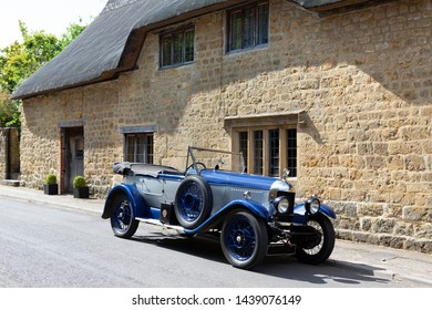 ILMINSTER, SOMERSET, ENGLAND - JUNE 6, 2018: Classic Blue Morris Oxford motor car outside a country cottage.