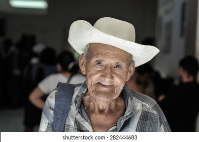 Ilobasco, Caba�±as / El Salvador - December 19, 2012: An elder man wearing a traditional framer hat walks out of a public health clinic after a doctor's appointment.