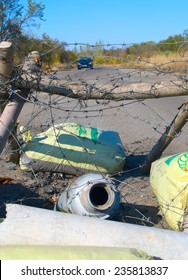ILOVAYSK, DONBASS, OCT 9: GRAD missile stuck in the road in Ilovaysk on 9 October 2014. Road sign showing how much kilometers left to Donestk and Khartsyzk.