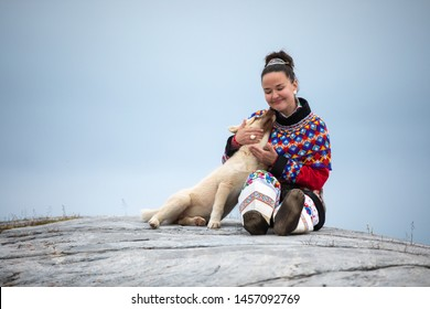 Ilulissat, Greenland - Jul 31, 2018: Young inuit woman in traditional clothing posing for photos in a small Greenlandish village.