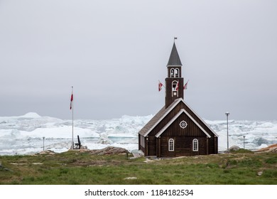 Ilulissat, Greenland - July 1, 2018: Exterior view of the old wooden Zion's Church with icebergs in the background