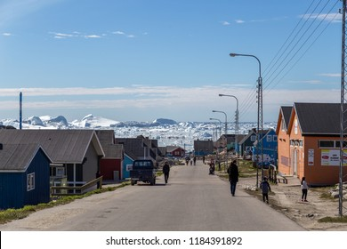 Ilulissat, Greenland - June 30, 2018: Street with coloful wooden houses and icebergs in the background