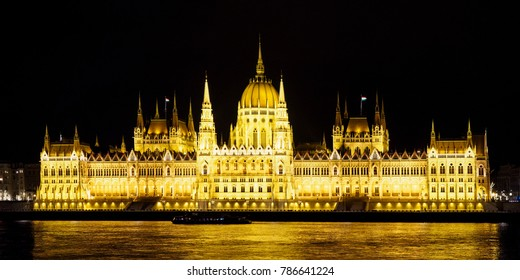 Iluminated Hungarian parliament on Danube riverside by night in Budapest. Travel destinations.