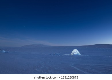 Iluminated igloo during a cold winter nights with bright moonshine